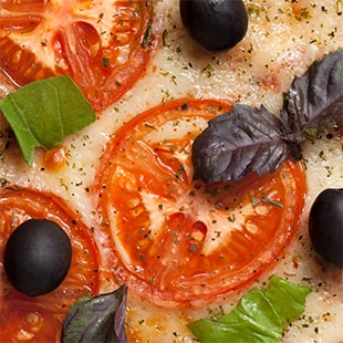 Closeup of pizza with tomatoes and black olives.
